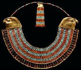 This beaded collar has a beaded pattern of alternating rows of turquoise and carnelian.  Both ends terminate with gold falcon heads.  Attached where the necklace hits the back of the neck is a counterpoise with the same characteristics as the front, save for it has a single gold falcon head.