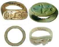 Four rings of various materials and shapes.  Top left:  a gold seal ring with a flat signet bearing the Horus Name of Amenhotep I, Ka-Djoser-Re.  Top right:  another seal ring made out of amazonite (feldspar) with a flat signet bearing the Horus name of Amenhotep III (Neb-Maat-Re).  Bottom left:  a simple tubular ring made of steatite.  Bottom right:  a tubular ring made of steatite with the Eye of Horus carved into the signet.